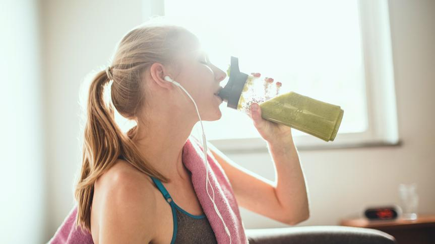 Young woman getting having her green smoothie after training.
