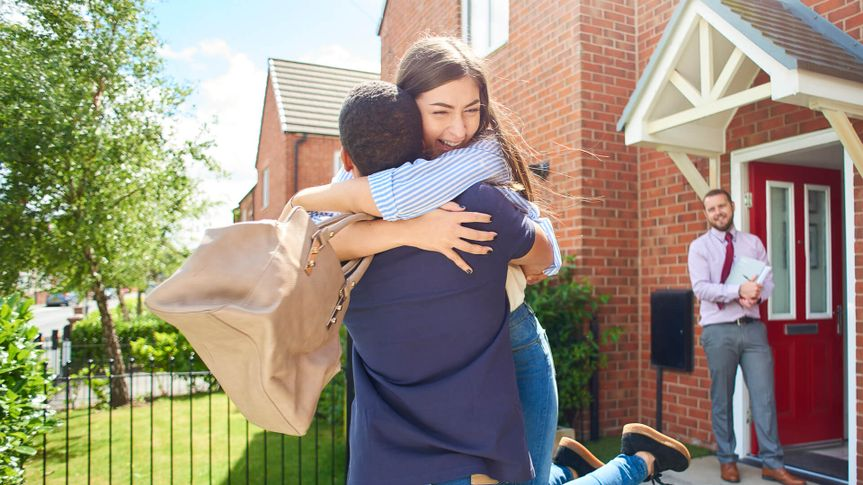 a couple embrace  in front of their new home , in the background an estate agent looks on happily.
