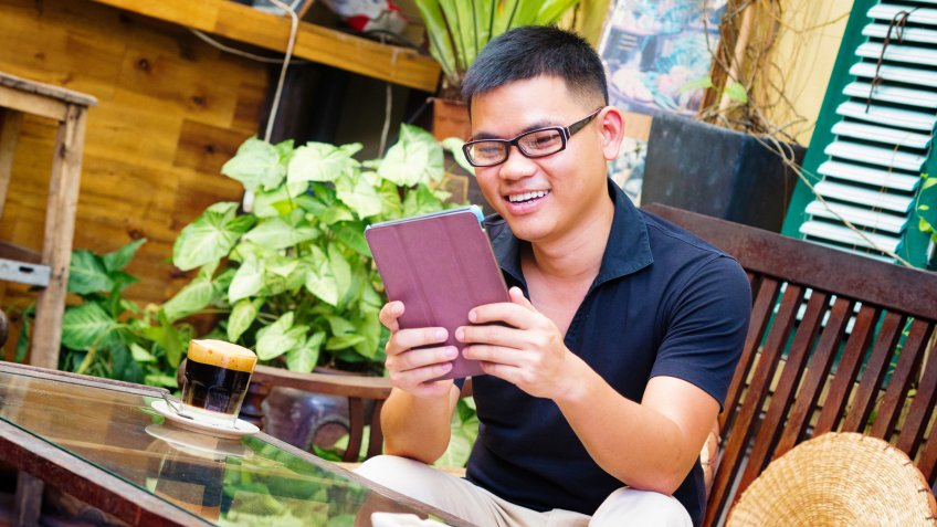Young Vietnamese male entrepreneur smiling at what he sees on his tablet in Hanoi cafe.