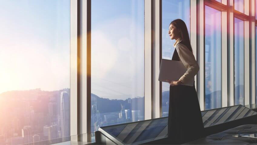 Successful female office worker with net-book is standing in skyscraper interior against big window with city view on background.