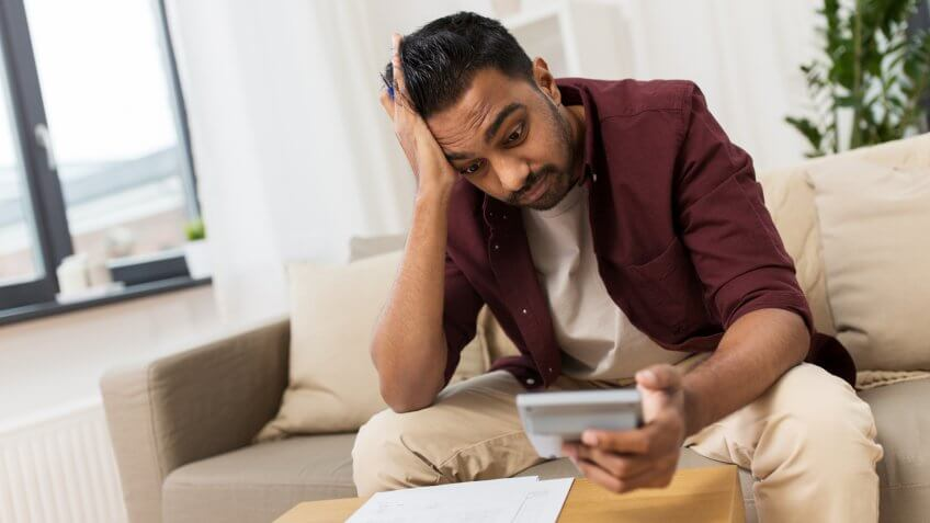 business, accounting, finances and people concept - confused man with papers and calculator at home.