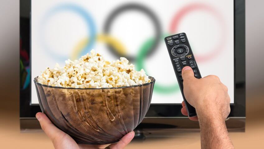 Man is watching sports games on TV and holds remote controller and popcorn in hands.
