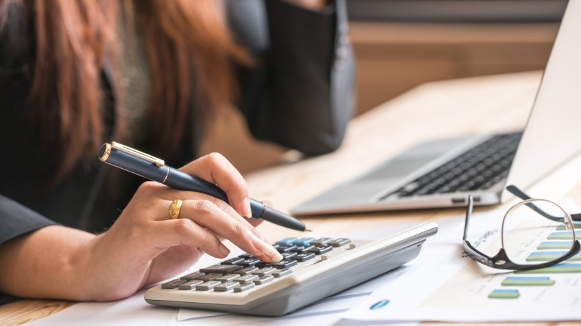 Close up of female accountant or banker making calculations.