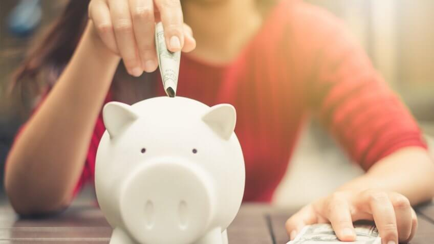 woman inserting cash into a piggy bank