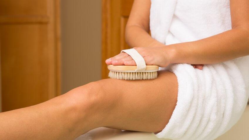 Sitting woman's arm holding dry brush to top of outstretched leg.