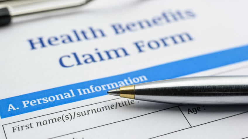 close-up of pen on top of health benefits claim form