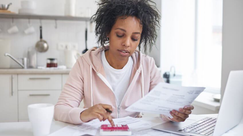 woman reviewing her billing statements and using calculator