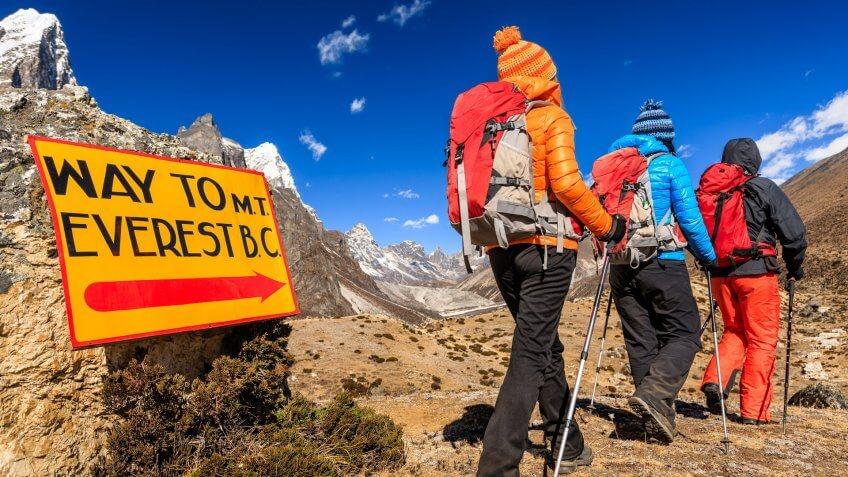 "Group of three trekkers passing signpost ""Way to Mount Everest Base Camp"" - Mount Everest (Sagarmatha) National Park."
