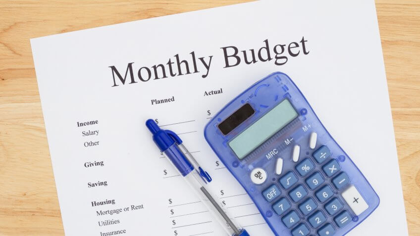 monthly budget sheet with pen and calculator