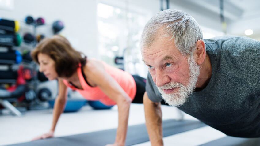 senior-couple-exercising-in-gym-healthy