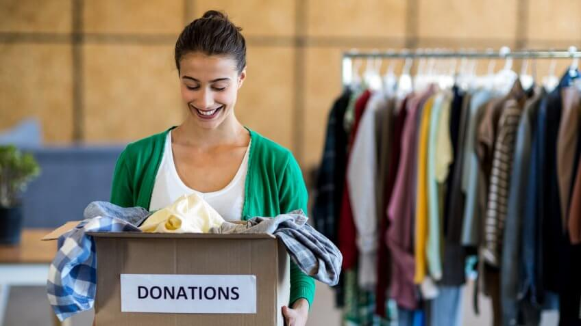 smiling woman holding a box of clothing donations