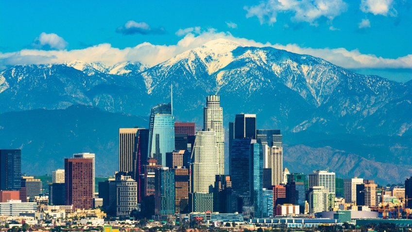 Downtown Los Angeles with the new Wilshire Grand skyscraper, Los Angeles' tallest building by pinnacle, and with the snow-capped San Gabriel Mountains in the background.