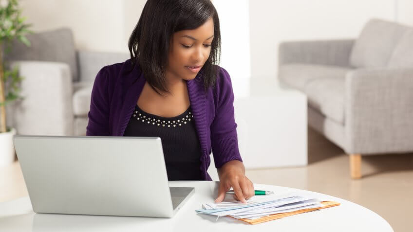 woman checking her billing statements at the desk in front of laptop