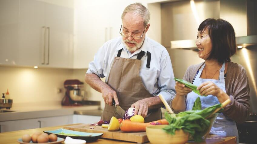 mature man and woman cooking in kitchen