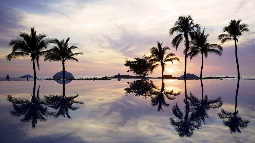 The sun sets over the ocean and an infinity pool in Mexico.