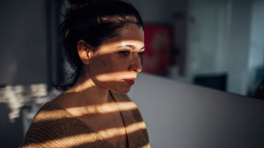 Portrait of a sad young woman in her apartment, with a sun on her face, that is breaking through the window blinds // wide photo dimensions.