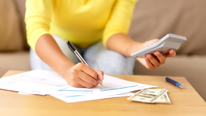 woman calculating bills with calculator and cash