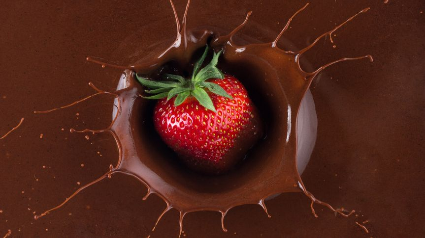 strawberry being dipped in chocolate