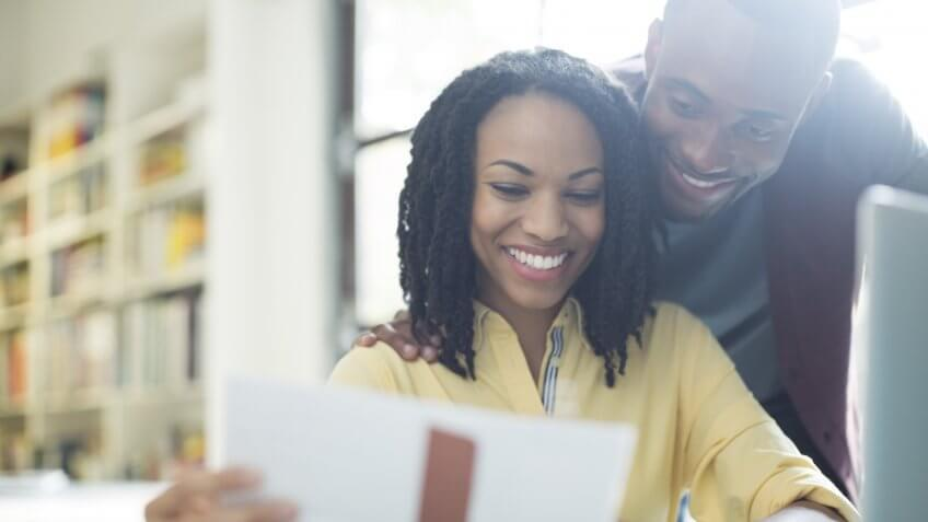 Happy couple reading paperwork at laptop