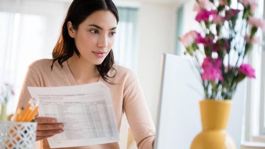 Hispanic woman paying bills on laptop.