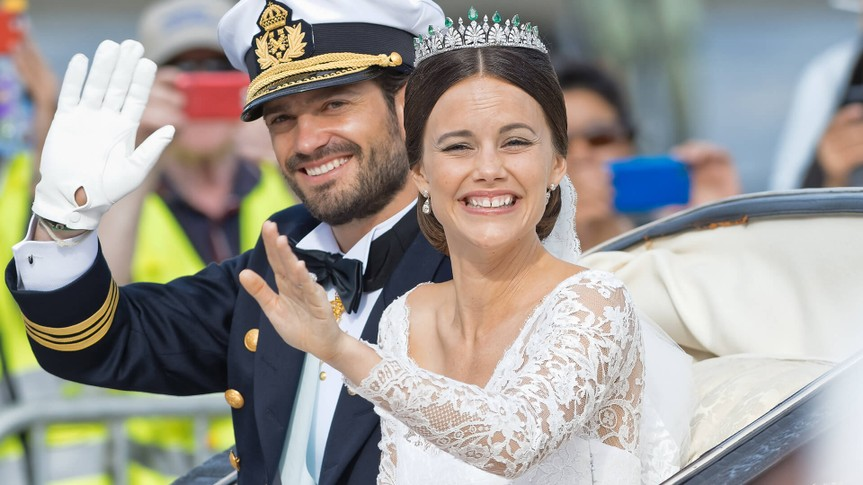 STOCKHOLM - JUN 13, 2015: Prince Carl-Philip and Princess Sofia laughing and waving in the royal carriage after the wedding with the crowd cheering.