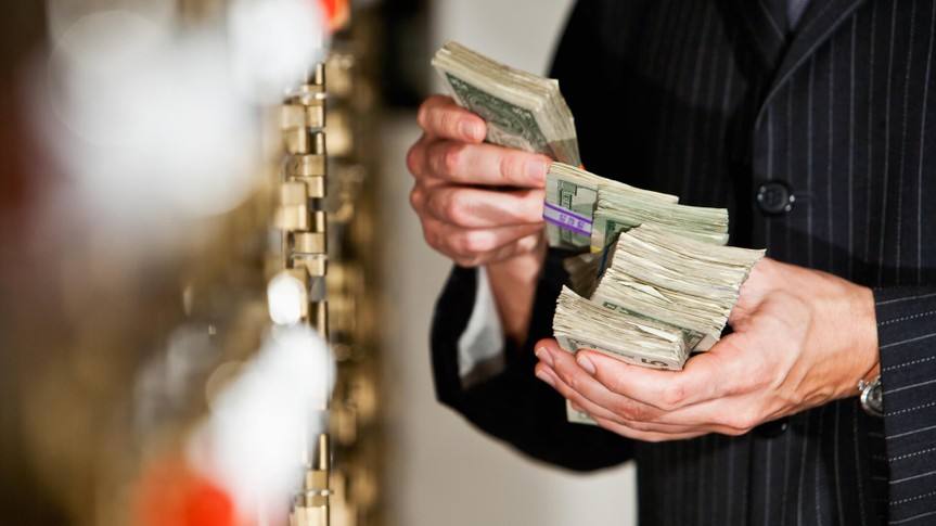 Man holding big stack of US paper currency by safety deposit boxes.