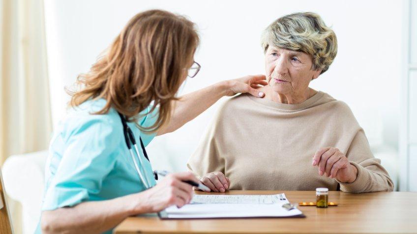 View of female doctor diagnosing elder woman.