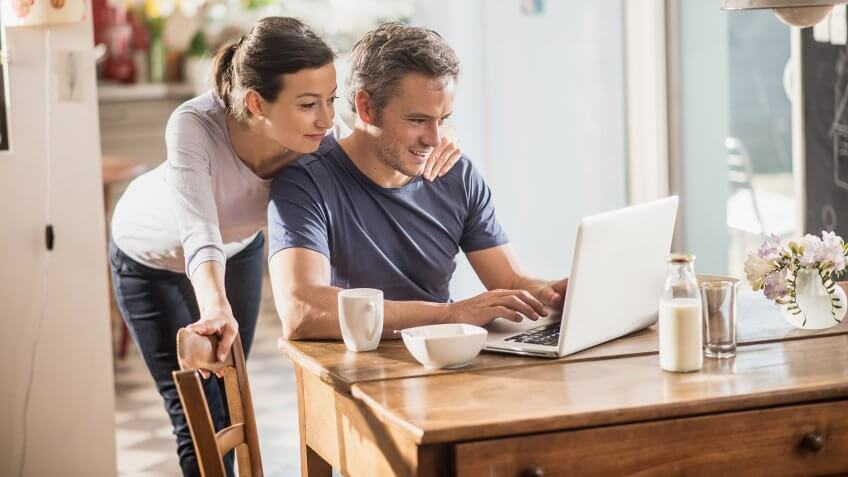 Nice thirty year couple using a laptop while having breakfast in the kitchen, they are wearing casual clothes and th man has gray hair.