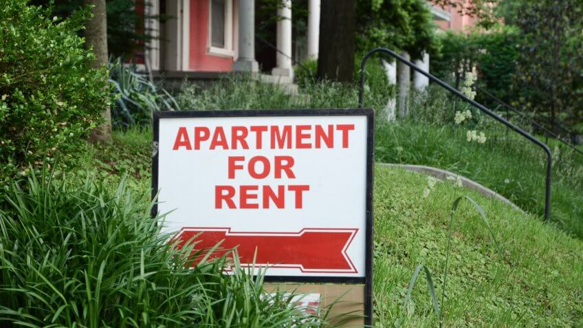 Apartment for rent sign displayed on residental street.