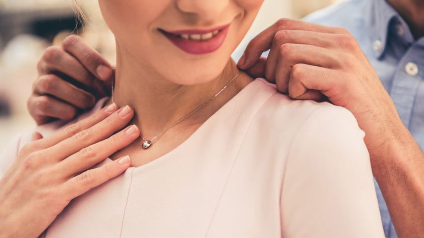 Cropped image of beautiful couple smiling while choosing jewelry in the shopping mall.