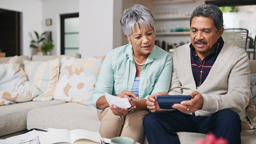 elderly couple working out a budget while sitting on the living room sofa.