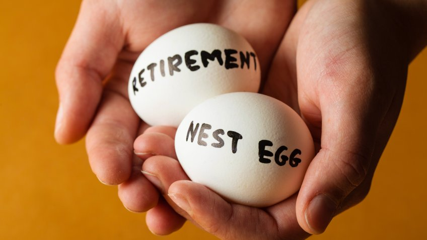 Hands Holding Two Eggs Marked Retirement And Nest Egg.