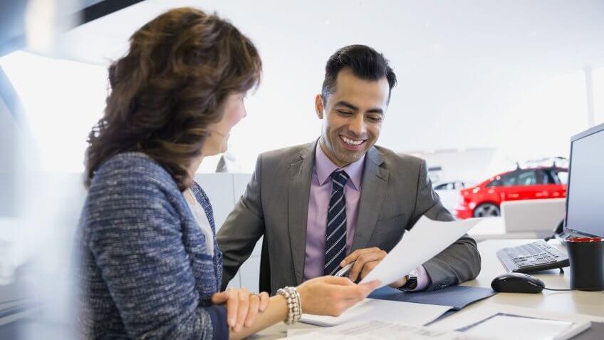 Salesman and woman finalizing paperwork in car dealership.