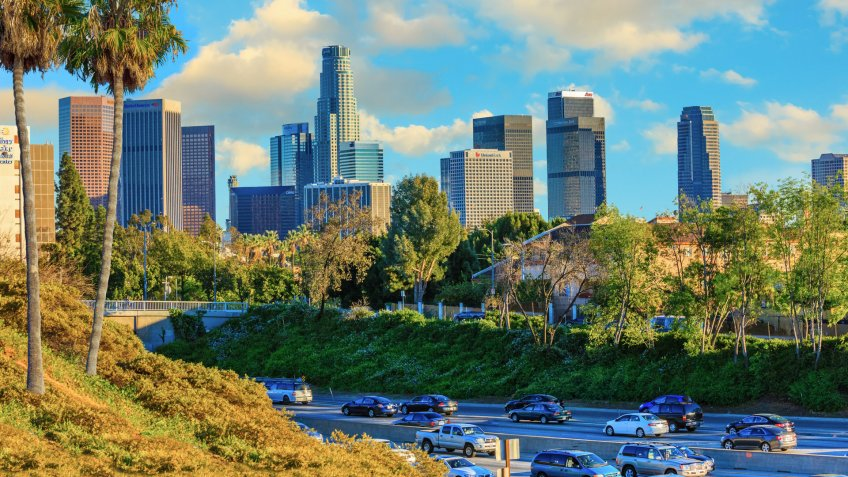 Palm trees and freeway traffic fills the foreground leading back to the skyscrapers of Los Angeles skyline with cloudscape above, California.