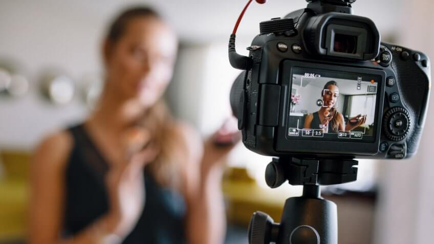 Woman making a video for her blog on cosmetics using a tripod mounted digital camera.