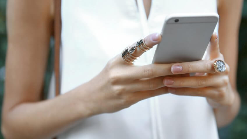 Female hands with phone and stylish rings, closeup.