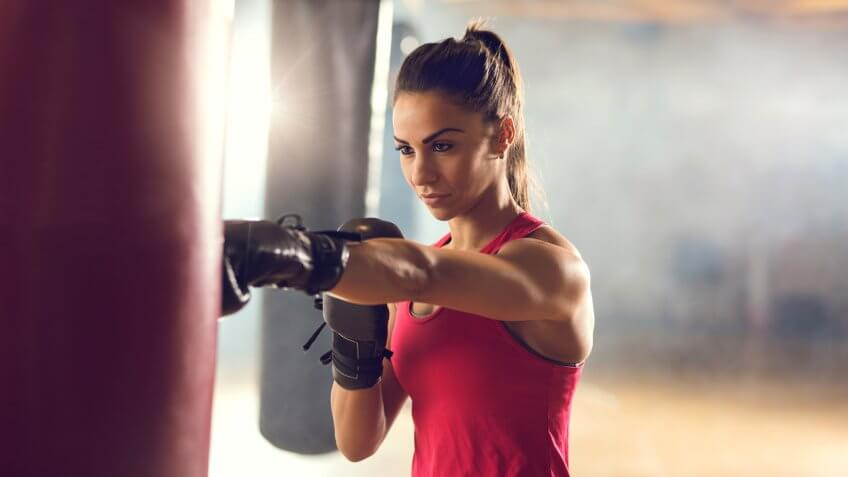 Young muscular build woman punching a bag on a boxing training in a gym.