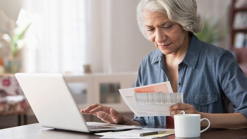 Older Black woman paying bills on laptop.
