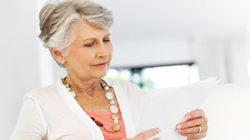 Senior woman reading over some documents.