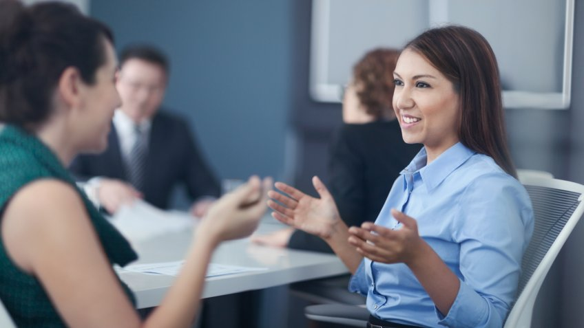 Women talking together in business office meeting.