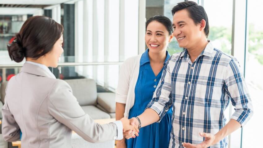 Husband shaking hands with the real estate agent.