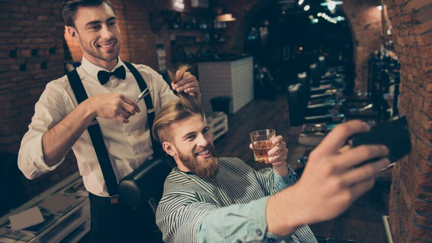 Smile! Cheerful handsome stylish red bearded guy is taking selfie photo at barber shop, classy dressed smiling stylist is making him a brand new haircut and posing also.