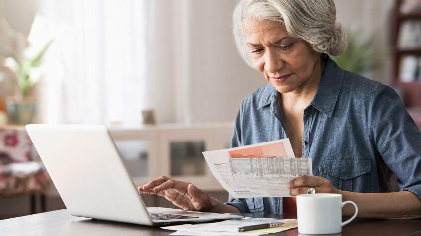 Older woman paying bills on laptop.