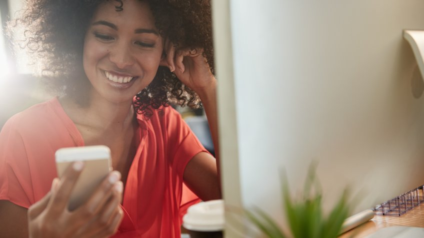 Shot of an attractive young woman using her mobile phone while sitting at her office desk.