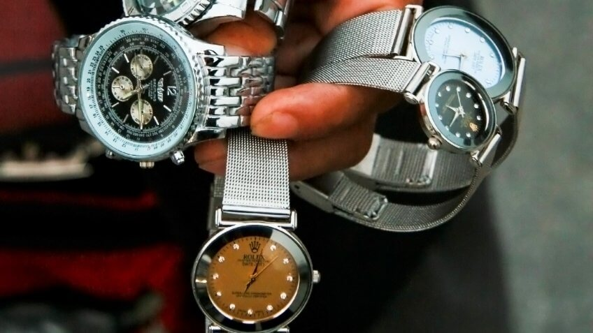 SHANGHAI, CHINA - OCTOBER 28: A Chinese salesman shows his merchandise of fake designer watches on the Bund in Shanghai, on October 28, 2007.