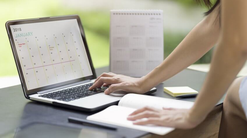 Woman planning agenda and schedule using calendar event planner.