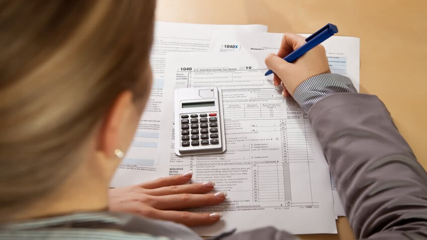 Woman hand filling income tax forms with calculator.