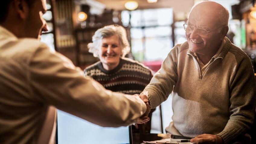 Smiling senior man shaking hands with financial advisor.