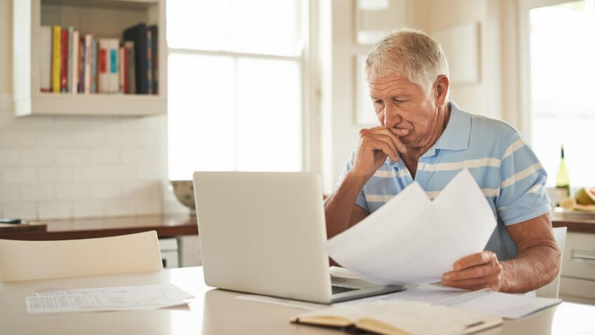 Shot of a senior man looking stressed while doing the household finances on a laptop in his kitchen.
