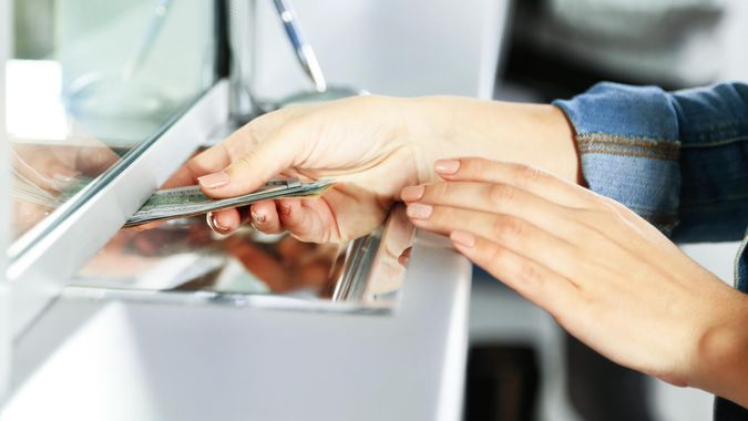 Female hand with money in cash department window.